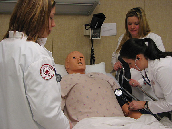 Nursing students test their knowledge on a dummy patient at Lower Columbia College. Photo by Wayne Hsieh.